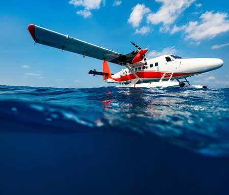 Split underwater photo of small seaplane on water