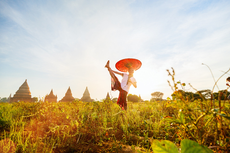 Happy young girl with traditional burmese parasol enjoying visit of ancient temples in Bagan Myanmar at sunset