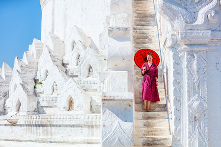 Young woman with traditional burmese umbrella at beautiful white Hsinbyume pagoda in Mingun Myanmar