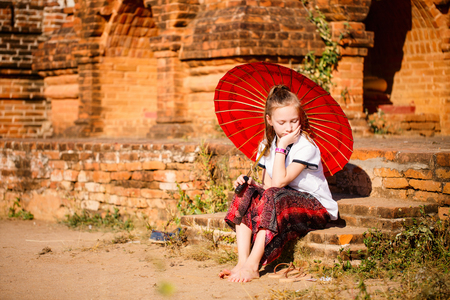 Young girl with traditional burmese parasol visiting ancient temples in Bagan Myanmar Imagens