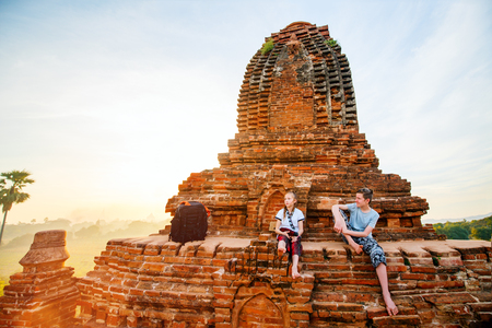 Kids brother and sister enjoying rooftop sunset view over Old Bagan in Myanmar