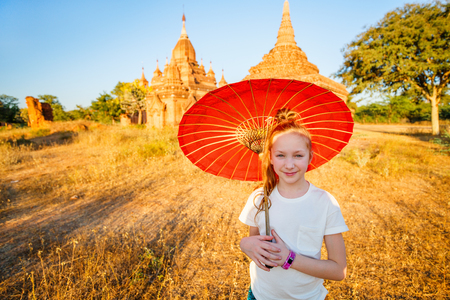 Young girl with traditional burmese parasol visiting ancient temples in Bagan Myanmar at sunset