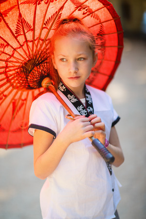 Young girl with traditional burmese parasol outdoors