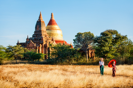 Family of mother and daughter visiting ancient temples in Bagan Archeological area in Myanmar