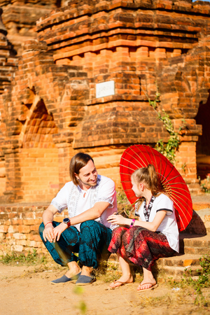 Family of father and daughter visiting ancient temples in Bagan Archeological area in Myanmar