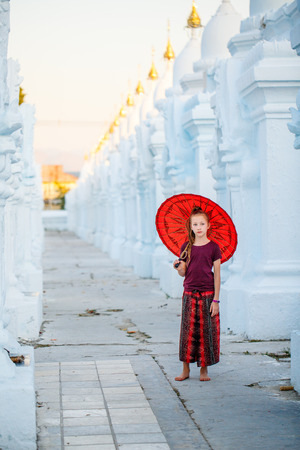 Young girl with traditional burmese umbrella at beautiful white Kuthodaw Pagoda in Mandalay Myanmar Stock fotó