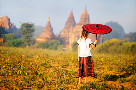 Back view of young girl with traditional burmese parasol visiting ancient temples in Bagan Myanmar Banco de Imagens