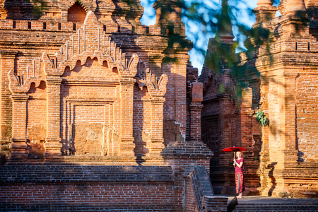 Young girl with traditional burmese parasol visiting ancient temples in Bagan Myanmar Stock Photo