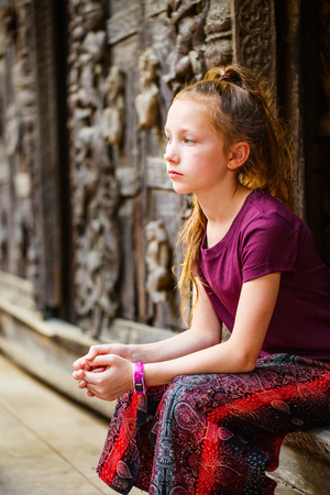 Young girl visiting historic Shwenandaw Buddhist monastery located in Mandalay Myanmar Stockfoto