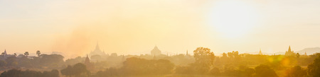 Panorama of scenic sunset with Ananda temple silhouette and thousands of historic buddhist pagodas and stupas in Bagan Archeological area in Myanmar