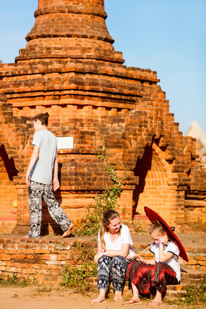 Family of mother and kids visiting ancient temples in Bagan Archeological area in Myanmar
