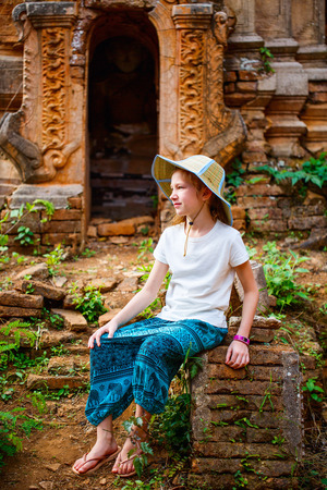 Young girl visiting hundrets of centuries old stupas in Indein near lake Inle in Myanmar
