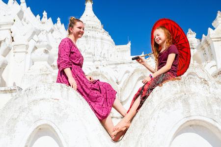 Family of mother and daughter enjoying visit to beautiful white Hsinbyume pagoda in Mingun Myanmar