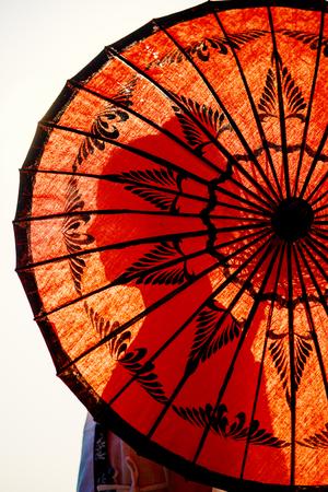 Young girl silhouette seen through traditional burmese umbrella