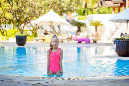 Adorable niña en la piscina durante las vacaciones de verano