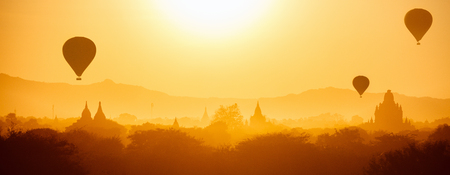 Stunning sunrise view of hot air balloons fly over thousands of ancient pagodas at morning in Bagan Myanmar
