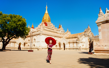 Young girl with traditional burmese parasol visiting Ananda Pagoda one of Bagan most beautiful temples Banco de Imagens