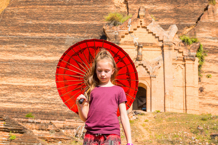 Young girl with traditional burmese umbrella visiting unfinished Mingun paya temple in Myanmar