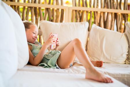 Adorable niña jugando en un dispositivo de juego portátil o teléfono Foto de archivo
