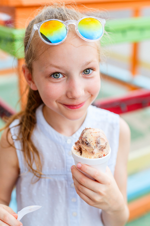 Adorable girl eating chocolate ice cream outdoors on summer day 免版税图像