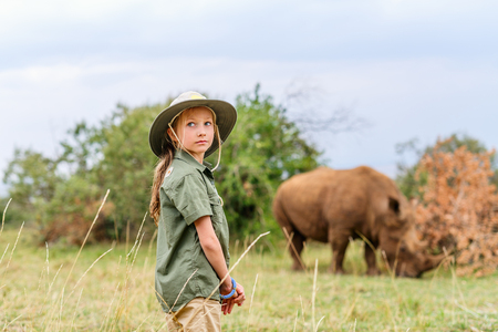 Cute little girl on walking safari in Kenya observing white rhinos Standard-Bild - 124043221