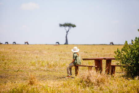 Little girl witnessing great migration of wildebeests in Masai Mara National park in Kenya Stock Photo