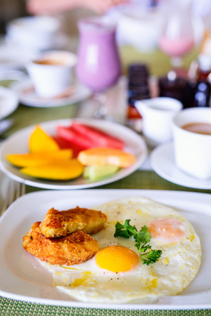 Delicious breakfast with fried eggs, potato hash and fruits Stock Photo