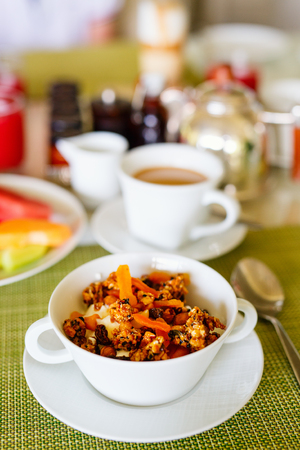 Healthy breakfast bowl of homemade granola from several types of cereals and nuts