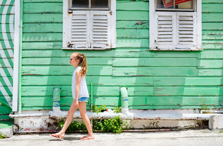 Little girl outdoors against colorful house on Barbados island in Caribbean