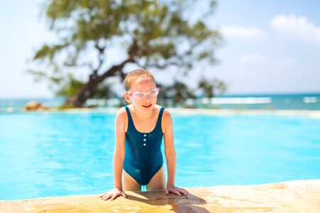 Adorable little girl at swimming pool having fun during summer vacation