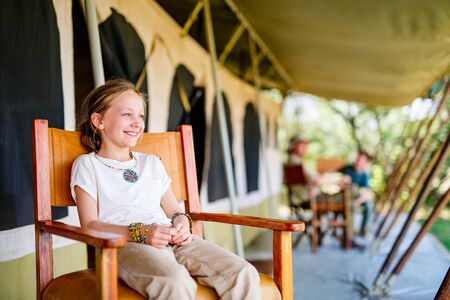 Little girl with her family on safari enjoying  luxury vacation in Africa Stock Photo
