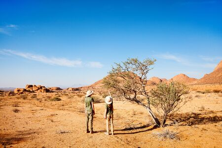 Kids brother and sister hiking in Spitzkoppe with unique rock formations in Damaraland Namibia Stok Fotoğraf