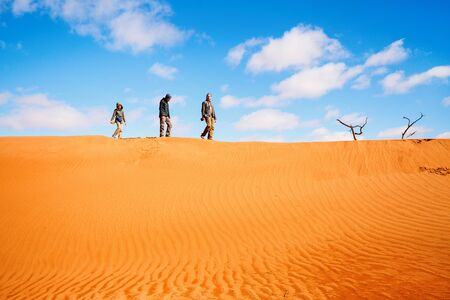 Family of father and two kids climbing up red sand dune in Namib desert Stok Fotoğraf