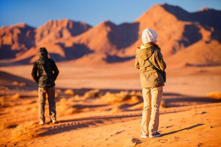 Back view of two kids brother and sister enjoying stunning view over Tiras mountains in Namib desert during sunset