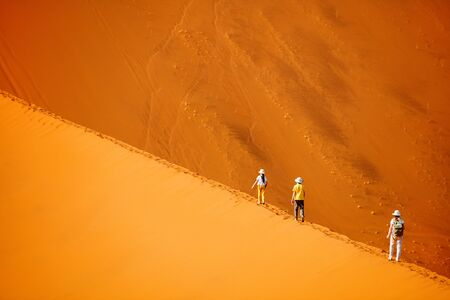 Family of mother and two kids climbing up famous red sand dune Big Daddy in Sossusvlei Namibia Stok Fotoğraf