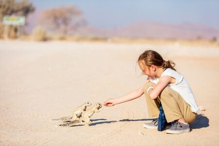 Adorable young girl feeding little ground squirrels outdoors Stok Fotoğraf