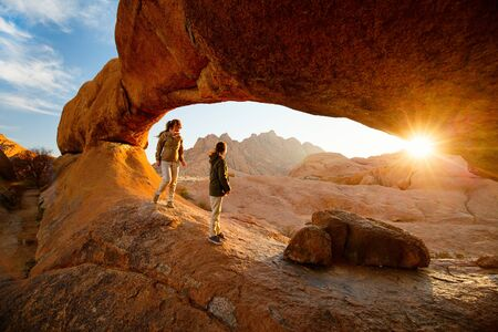 Family mother and daughter enjoying sunrise in Spitzkoppe area with picturesque stone arches and unique rock formations in Damaraland Namibia