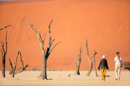 Back view of family mother and daughter walking among dead camelthorn trees surrounded by red dunes in Deadvlei in Namibia