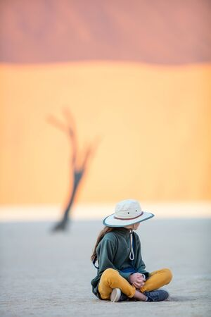 Young girl against dead camelthorn trees and red dunes in Deadvlei in Namibia