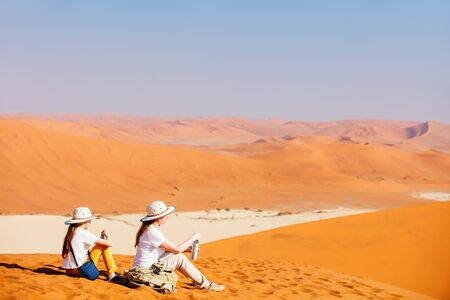 Family of mother and daughter resting while climbing up famous red sand dune Big Daddy in Sossusvlei Namibia