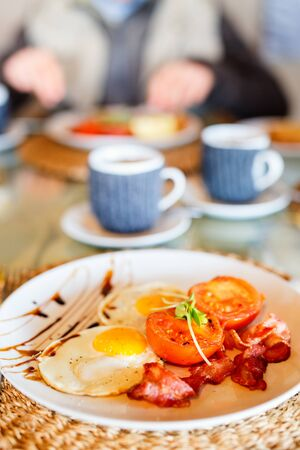 Delicious breakfast with fried eggs, bacon and vegetables Stok Fotoğraf