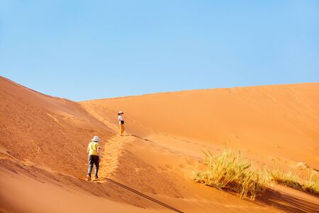 Kids brother and sister climbing up famous red sand dune Big Daddy  in Sossusvlei Namibia Stok Fotoğraf