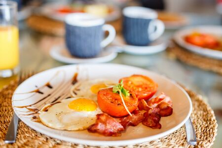 Delicious breakfast with fried eggs, bacon and vegetables 写真素材