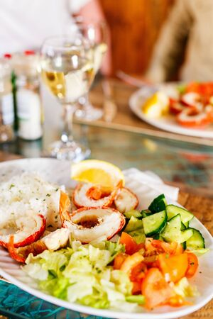 Grilled shrimps and fresh green salad served for lunch 写真素材