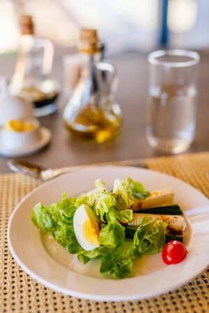 Delicious green salad, veggies and boiled egg served for lunch