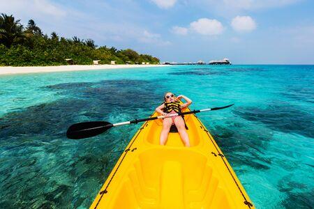 Little girl enjoying paddling in kayak at tropical ocean water during summer vacation
