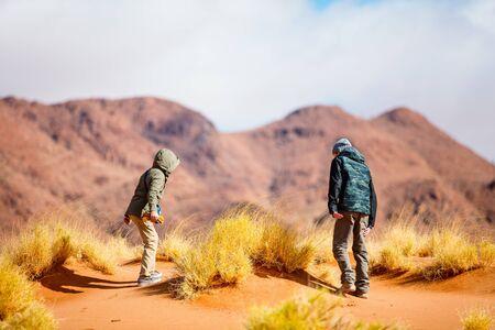 Two kids brother and sister enjoying stunning view over Tiras mountains in Namib desert during sunset