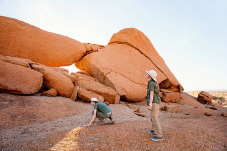 Kids brother and sister hiking in Spitzkoppe with unique rock formations in Damaraland Namibia Reklamní fotografie