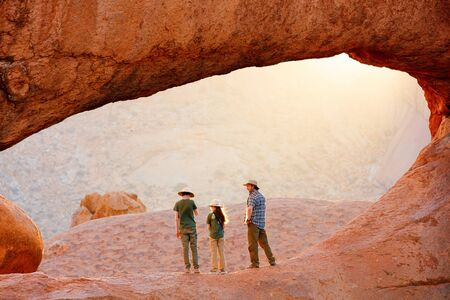 Family father and two kids hiking in Spitzkoppe area with picturesque stone arches and unique rock formations in Damaraland Namibia