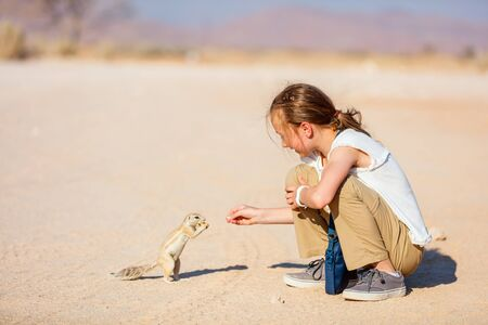 Adorable young girl feeding little ground squirrels outdoors 写真素材